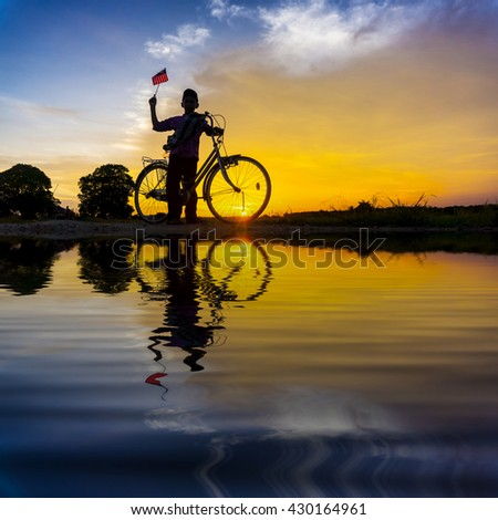 silhouette boy holding the malaysia flag during dramatic sunset and water reflection