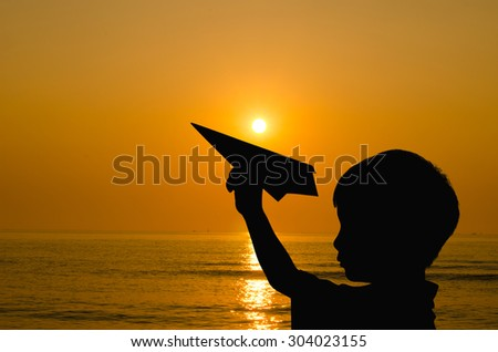 Silhouette boy playing with paper airplane and rising sun on bea - stock photo
