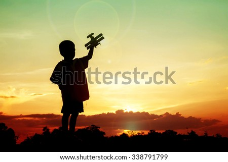 silhouette boy playing with toy airplane sunset - stock photo