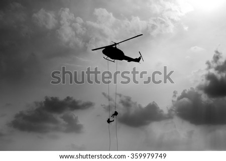 Silhouette Brave soldiers operating out assault by soldiers rappelling from a helicopter - stock photo