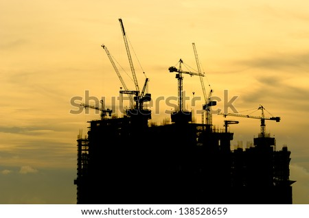 Silhouette Building crane and building under construction against evening cloudy sky - stock photo