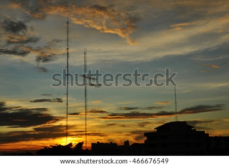 Silhouette buildings and telecom towers with colorful sky at the sunset in background.