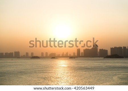 Silhouette buildings of a city with reflection in water. China - stock photo