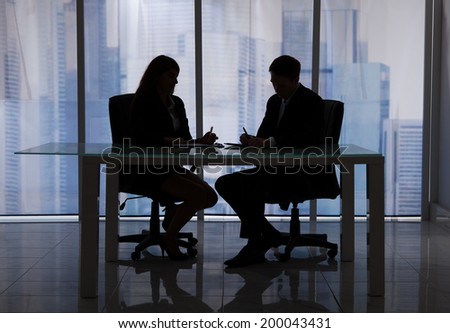 Silhouette businessman and businesswoman discussing at desk in office - stock photo