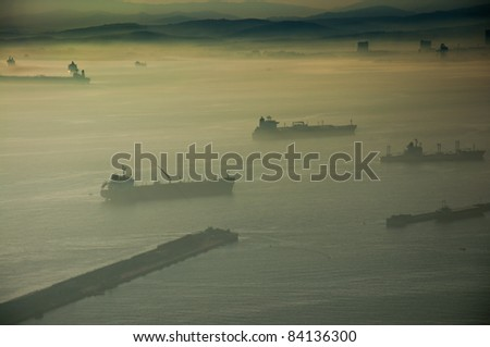 Silhouette cargo ship due to the fog