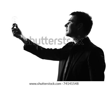 silhouette caucasian business man  holding light bulb expressing behavior full length on studio isolated white background - stock photo