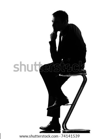 silhouette caucasian business man thinking pensive sititting on foot stool full length on studio isolated white background - stock photo