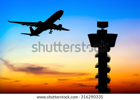 Silhouette commercial airplane take off over airport control tower at sunset - stock photo