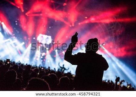 Silhouette Concert Person on Shoulders in Crowd with hands up at a Music Festival - Backlit with Lighting.