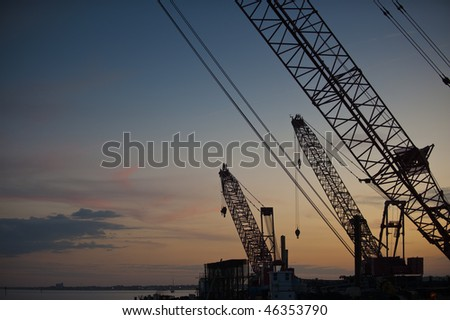 Silhouette construction crane sunset background - stock photo