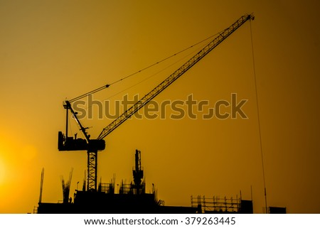 silhouette construction crane working in the evening light