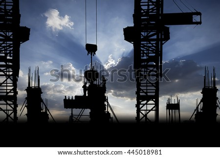 Silhouette Construction with workers and building on vibrant ray of light sky background - stock photo