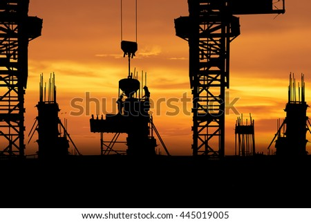 Silhouette Construction with workers and building vibrant orange sky background - stock photo