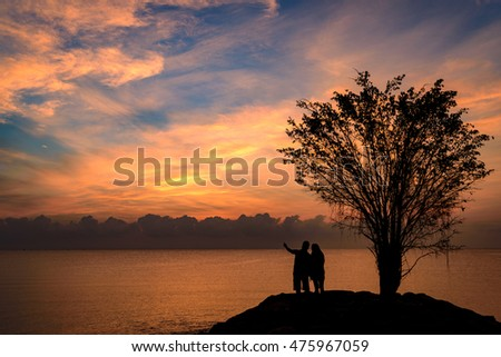 silhouette couple holding hand and point to the sun during sunrise with very beautiful sky