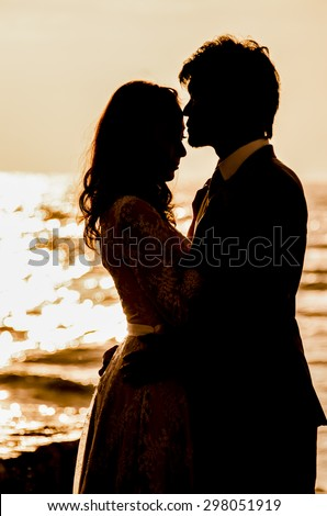 silhouette couple love at sea side morning - stock photo