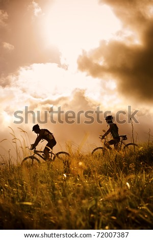 silhouette couple mountainbike riding outdoors at sunset - stock photo