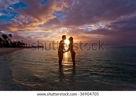 silhouette couple on beach flirting at sunset on tropical honeymoon vacation - stock photo