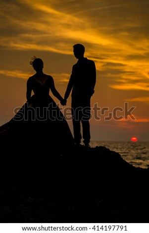 Silhouette couple's taking a photo prewedding before sunset on the beach rock , Phuket Thailand.