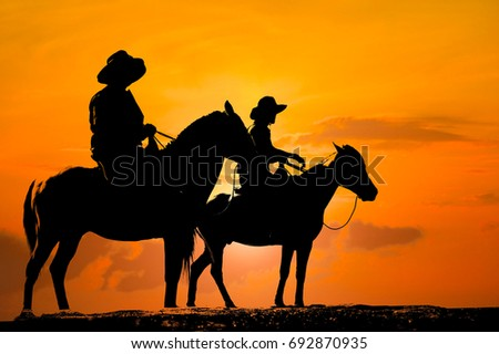 silhouette Cowboy riding a horse on sunrise