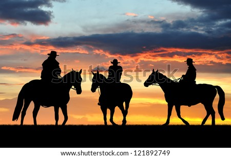Silhouette cowboys with horses in the sunset - stock photo