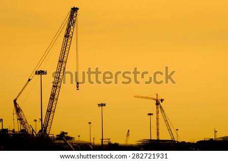 Silhouette crane construction oil refinery - stock photo