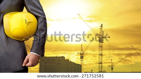 Silhouette Crane lifts load engineer hold yellow helmet for workers security on background of new highrise apartment buildings and construction cranes on backdrop of evening sunset cloudy sky  - stock photo
