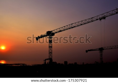 Silhouette cranes on top of under construction building at sunset