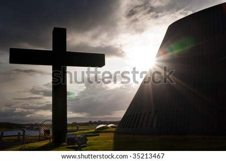 Silhouette cross with dramatic skylight reflecting at the background - stock photo