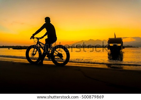 silhouette cyclist and amazing sunrise at gili island with rinjani mount background
