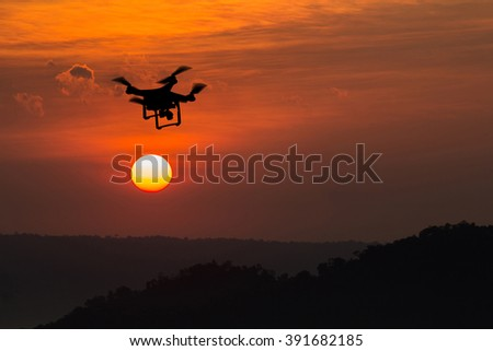 silhouette drone on sunset./ quadcopter at sunset - stock photo