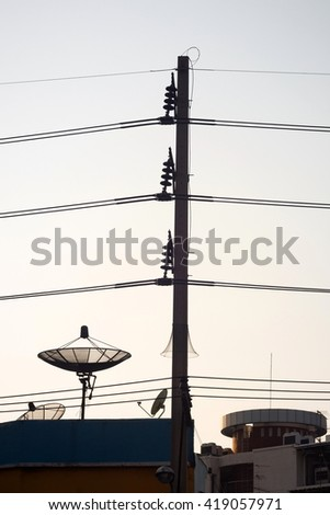 Silhouette electric pole and satellite dish in the city during sunset.