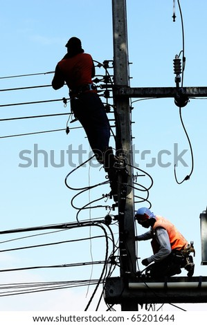 Silhouette Electrician Man on electric poles.  Electrical repairs are made to restore them to normal. - stock photo