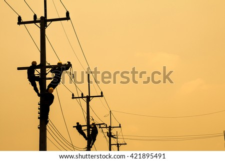 silhouette Electrician works in the height. - stock photo