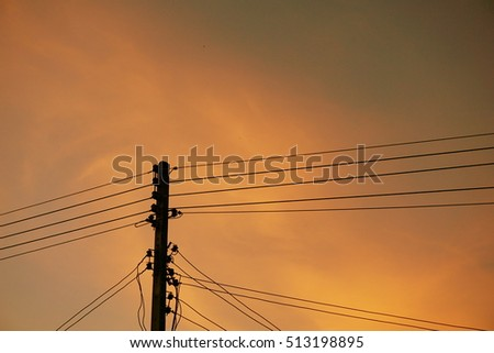 Silhouette electricity power lines over sunset orange sky with copy space background