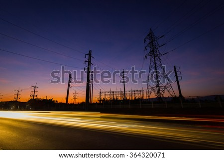 silhouette electricity pylons and power plant with light trails in the evening, Chiang Rai, Thailand. - stock photo