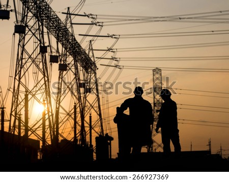 silhouette engineer looking construction site over Blurred substation - stock photo