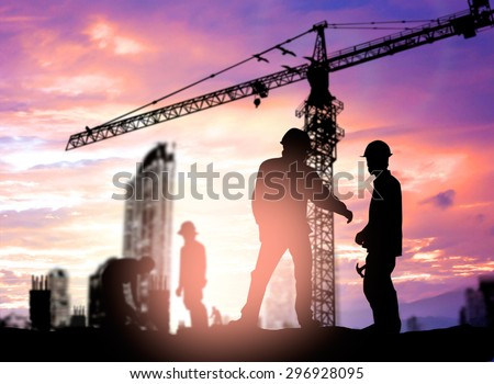 Silhouette engineer looking construction worker under tower crane in a building site over Blurred construction worker on construction site - stock photo