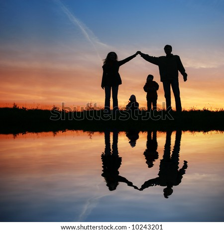 silhouette family house on sunset water - stock photo
