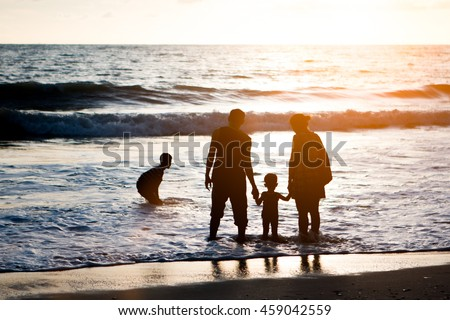 Silhouette family mother, father and young son holding hands, taking a swim in the sea for the first time the children over blurred beautiful nature.Concept friendly family.flare light.selected focus