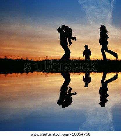 silhouette family of four and water - stock photo