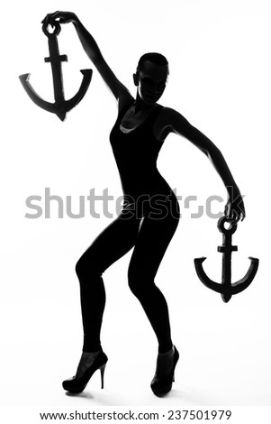 Silhouette fashion slim girl dancing in high heels with an anchor - stock photo