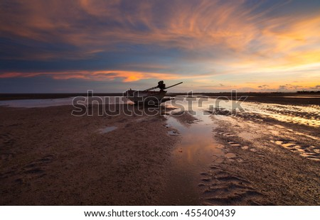 silhouette fisherman boat  on yellow and orange  sunset  - stock photo
