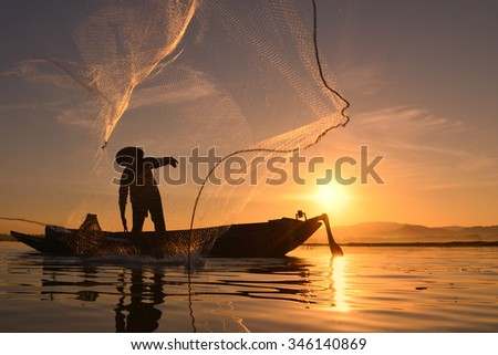 Silhouette Fisherman in action fishing . - stock photo
