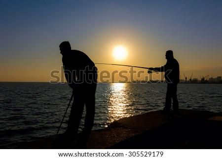 Silhouette fishermen fishing in the sea - stock photo