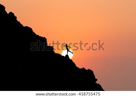 Silhouette Freedom-young man is jumping over rocky.