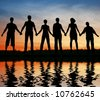 silhouette friends. sunset water - stock photo