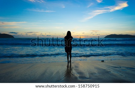 silhouette girl at the beach - stock photo