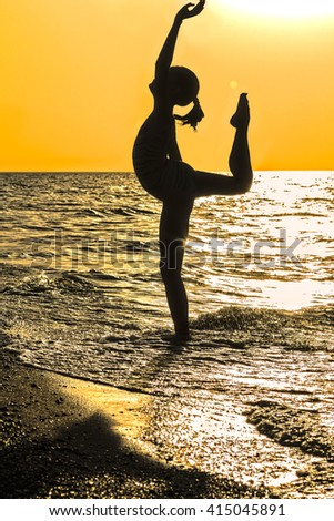 Silhouette girl on beach on the background of orange sunset. Girl doing gymnastic exercise - stock photo