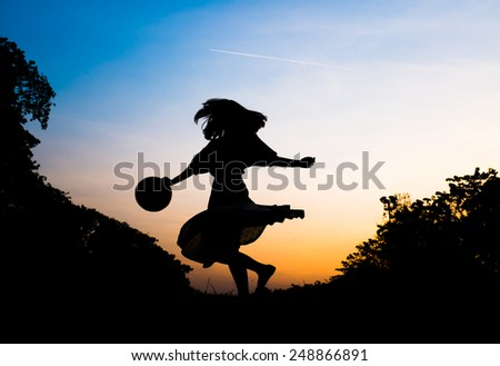 silhouette girl playing in park at sunset - stock photo