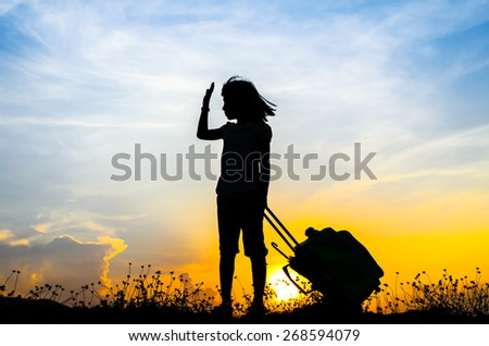Silhouette Girl with a suitcase with sun set. - stock photo